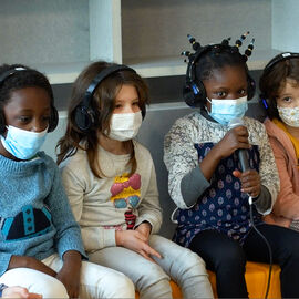 Une petite fille parle dans un micro assise à côté de ses camarades de classe