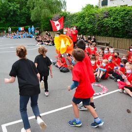 Des enfants habillés en rouge portent une flamme factice devant un public d'enfants