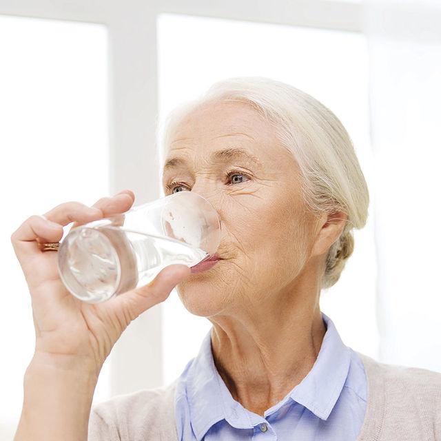 Une personne âgée boit un verre d'eau.