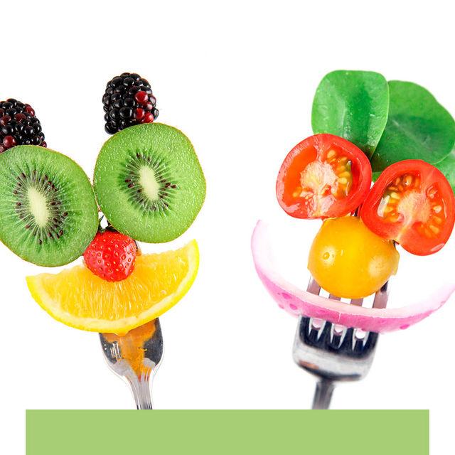 Personnages en fruits et en légumes sur des fourchettes